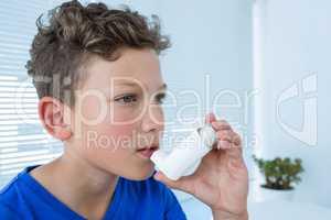 Boy using asthma pump