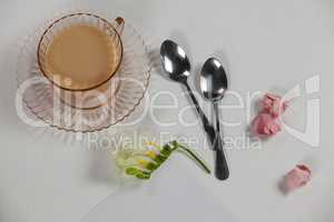Cup of tea, spoons, blank page, paper balls and flower