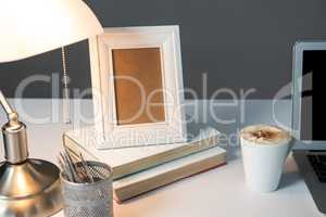Picture frame, cup of coffee with books and table lamp