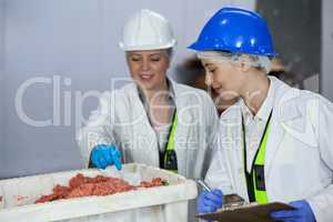 Technician writing on clipboard while examining meat