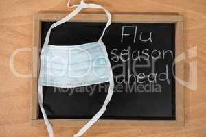 Flue season ahead written on chalk board with medical mask