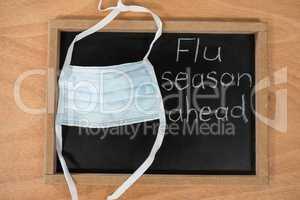 Flue season ahead written on chalk board with medical mask