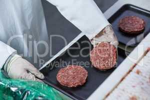 Butcher arranging hamburger patty on tray
