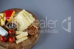 Variety of cheese with cherry tomato, sauce and spices on wooden board