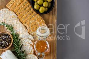 Variety of cheese with olives, honey, rosemary, walnuts and crackers