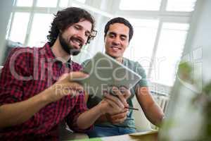 Graphic designers using digital tablet at desk