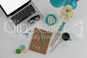 Laptop, spectacles, earphones, flowers, macaroons and office desk tops