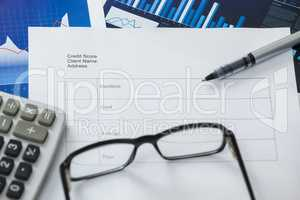 Paper document with business graph, pen, calculator and spectacle
