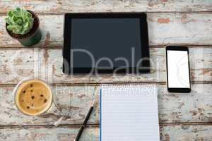 Digital tablet with smartphone, pot plant, pen, notepad and coffee cup
