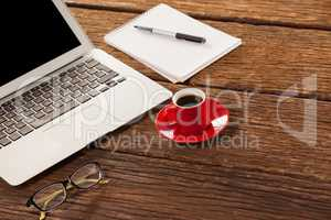 Laptop, spectacle and notepad with cup of coffee