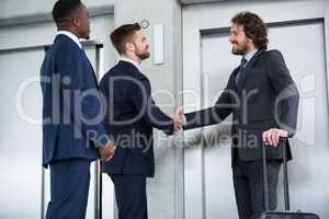 Businessmen shaking hands while waiting for elevator