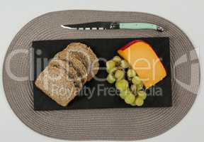 Brown bread, grapes and gouda cheese with knife on slate board