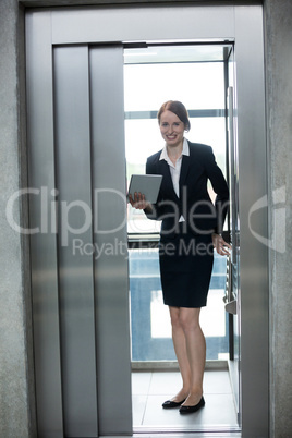 Businesswoman standing in an elevator holding a digital tablet