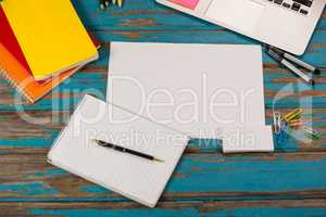 Notepad, blank page, diaries, pens, color pencils, laptop and paper pins