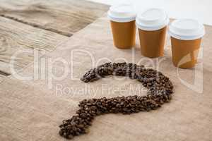 Coffee beans arranged in question mark shape with disposable coffee cups