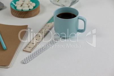 Coffee mug, ruler, diary, pen and pebbles