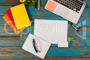 Notepad, blank page, spectacles, diaries, pens, color pencils, laptop and paper pins