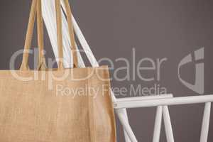Beige fabric bag hanging on a white chair
