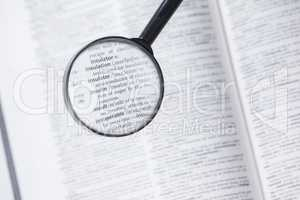 Dictionary page viewed through magnifying glass