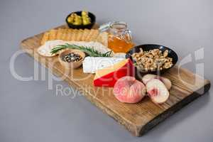 Variety of cheese with olives, peach, honey, rosemary, walnuts and crackers