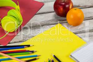Color pencils, notepad, placard, fruits and headphones