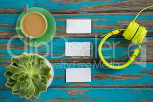 Coffee with headphones, sticky notes and pot plant on table