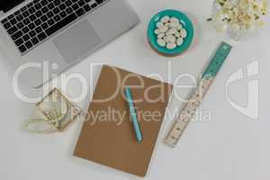 Laptop, pearl necklace, ruler, pen, diary and pebbles