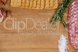 Ham, biscuits, rosemary and salt on chopping board