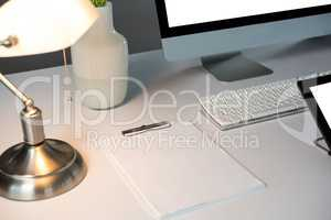 Desktop pc, and table lamp with blank paper sheets