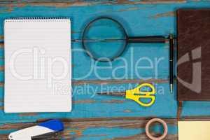 Notepad, magnifying glass, scissor, stapler, pen sellotape and diary