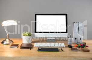 Desktop pc with table lamp and office stationery