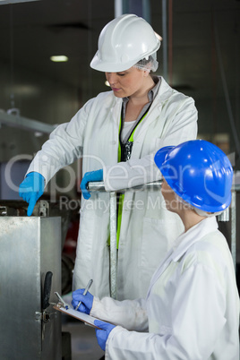 Female technician writing on notepad while examining meat processing machine