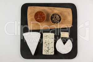 Sliced cheese, bowls of jam and spices on chopping board