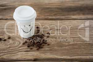 Coffee beans and disposable coffee cup with smiley face