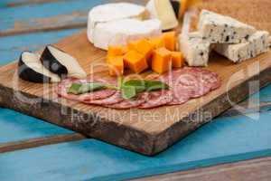 Ham with various cheese on chopping board