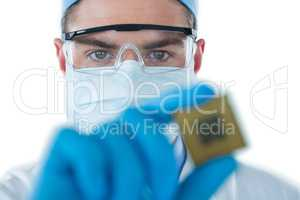 Doctor wearing protective glasses and surgical mask holding electronic chip