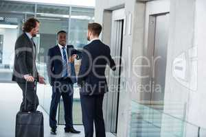 Businessmen talking while waiting for elevator