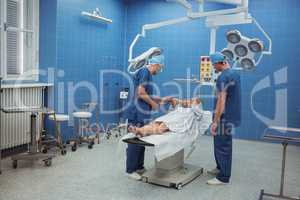 Surgeons interacting with patient during operation