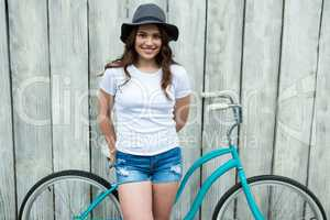 Happy woman in white t-shirt and hot pants with bicycle