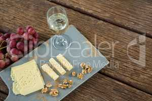 Pieces of cheese, walnut, grapes and glass of wine on tray