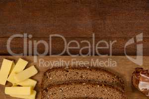 Slices of brown bread, meat and cheese on wooden chopping board