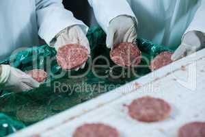 Butchers processing hamburger patty