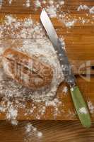 Bread loaf with knife on cutting board