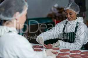 Female butchers processing hamburger patty