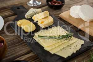 Variety of cheese and rosemary herbs on wooden table