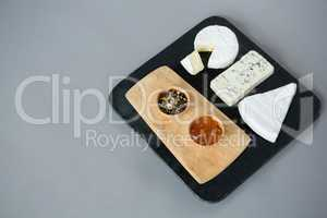 Variety of cheese with jam and fresh herbs on slate plate