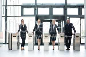 Businesspeople standing at turnstile gate