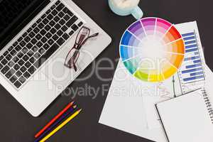 Laptop, spectacles, color pencils, color scheme chart, coffee cup, business graph and diary