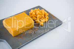 Block and cubes of cheese on chopping board