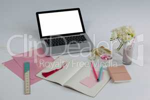 Laptop, diary, ruler, pages, sticky notes, flowers and pencil